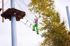 La muchacha adolescente se alza las escaleras en un parque de la cuerda Fotos de archivo libres de regalías