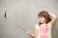 La muchacha adolescente se coloca con el monopod en manos Foto de archivo libre de regalías
