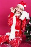 La muchacha adolescente se está sentando cerca del árbol de navidad Imagen de archivo libre de regalías