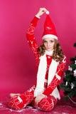 La muchacha adolescente se está sentando cerca del árbol de navidad Imágenes de archivo libres de regalías