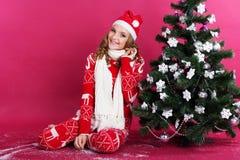 La muchacha adolescente se está sentando cerca del árbol de navidad Foto de archivo