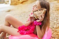 La muchacha adolescente se está sentando en el anillo de goma rosado con Fotografía de archivo libre de regalías