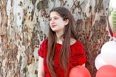 La muchacha adolescente se inclina en un árbol de eucalipto Foto de archivo