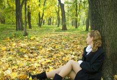 La muchacha adolescente se sienta bajo el árbol en parque Imagen de archivo