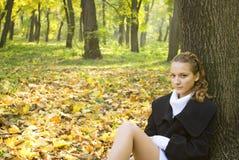 La muchacha adolescente se sienta bajo las hojas del árbol en parque Foto de archivo libre de regalías