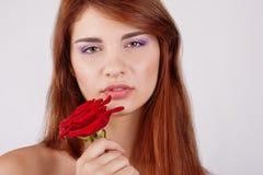 La muchacha adolescente sensual sostiene una rosa disponible Fotos de archivo libres de regalías