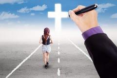 La muchacha adolescente sigue una cruz en el camino Foto de archivo