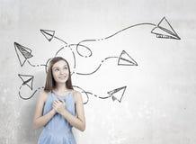 La muchacha adolescente soñadora, manos acerca al corazón, aviones de papel Foto de archivo libre de regalías