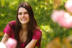 La muchacha adolescente sonriente atractiva se relaja en hierba verde de la primavera Foto de archivo