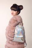 La muchacha adolescente sonriente de la morenita en abrigo de pieles rosado hace publicidad de la mochila, Imagen de archivo libre de regalías