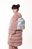 La muchacha adolescente sonriente de la morenita en abrigo de pieles rosado hace publicidad de la mochila, Imagenes de archivo