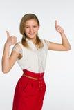 La muchacha adolescente sonriente detiene sus pulgares Foto de archivo libre de regalías
