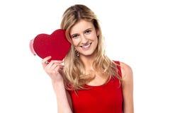 La muchacha adolescente sonriente que muestra el corazón forma el regalo a la cámara Imágenes de archivo libres de regalías