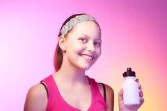 La muchacha adolescente sostiene la botella con agua y la sonrisa Imagenes de archivo