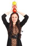 La muchacha adolescente sostiene tres manzanas en su cabeza Imagenes de archivo