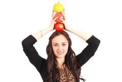 La muchacha adolescente sostiene tres manzanas en su cabeza Foto de archivo