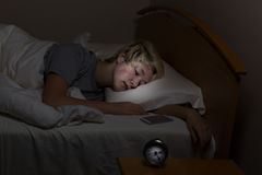 La muchacha adolescente tiene teléfono celular cerca incluso en su sueño Foto de archivo