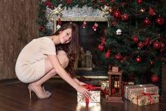 La muchacha adolescente toma un regalo del Año Nuevo de debajo agacharse feliz sonriente del árbol de navidad al lado de la chime Fotos de archivo libres de regalías