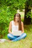 La muchacha adolescente trabaja con el ordenador portátil en la hierba Foto de archivo libre de regalías