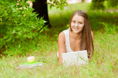 La muchacha adolescente trabaja con el ordenador portátil en la hierba Foto de archivo