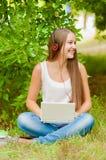 La muchacha adolescente trabaja con el ordenador portátil en la hierba Fotografía de archivo