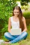La muchacha adolescente trabaja con el ordenador portátil en la hierba Fotografía de archivo libre de regalías