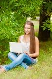 La muchacha adolescente trabaja con el ordenador portátil en la hierba Imagen de archivo