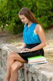 La muchacha adolescente trabaja con el ordenador portátil en auriculares y libros Foto de archivo