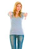 La muchacha adolescente trastornada que muestra los pulgares abajo gesticula Fotos de archivo libres de regalías