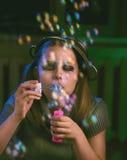 La muchacha adolescente triste sienta y sopla burbujas de jabón Fotografía de archivo