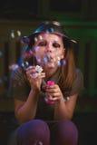 La muchacha adolescente triste sienta y sopla burbujas de jabón Imagenes de archivo