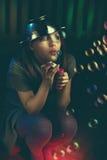 La muchacha adolescente triste sienta y sopla burbujas de jabón Foto de archivo libre de regalías