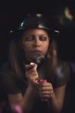 La muchacha adolescente triste sienta y sopla burbujas de jabón Imágenes de archivo libres de regalías