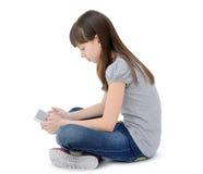 La muchacha adolescente utiliza un artilugio, aislado en el fondo blanco Imágenes de archivo libres de regalías