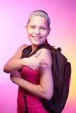 La muchacha adolescente va a la escuela con una mochila en ella detrás Imagenes de archivo
