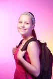La muchacha adolescente va a la escuela con una mochila en ella detrás Foto de archivo