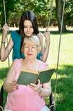 La muchacha adolescente y su abuela leyeron un libro en la vertical del parque Imagenes de archivo
