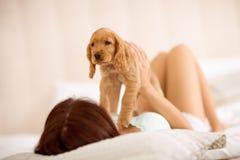 La muchacha adora su raza cocker spaniel del perrito Foto de archivo libre de regalías
