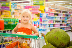 La muchacha adorable en carro de la compra mira las frutas gigantes del enchufe en la caja Foto de archivo libre de regalías