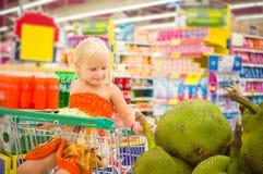La muchacha adorable en carro de la compra mira las frutas gigantes del enchufe en la caja Fotos de archivo