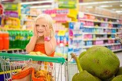 La muchacha adorable en carro de la compra mira las frutas gigantes del enchufe en la caja Imagenes de archivo