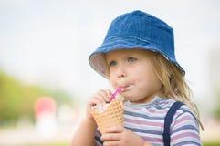 La muchacha adorable en sombrero azul come el helado Imágenes de archivo libres de regalías