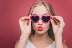 La muchacha adorable en vidrios con el borde rosado está pareciendo directa él está sosteniendo los vidrios en su borde cerca de  Imágenes de archivo libres de regalías