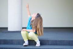 La muchacha adorable señala algo en el cielo que se sienta en strairs Fotos de archivo libres de regalías