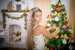 La muchacha adorna el árbol de navidad Fotografía de archivo libre de regalías