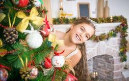 La muchacha adorna el árbol de navidad Foto de archivo