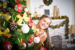 La muchacha adorna el árbol de navidad Fotos de archivo libres de regalías