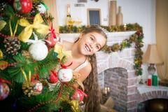 La muchacha adorna el árbol de navidad Imagen de archivo libre de regalías