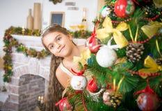 La muchacha adorna el árbol de navidad Imágenes de archivo libres de regalías