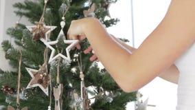 La muchacha adorna el árbol de navidad almacen de metraje de vídeo
